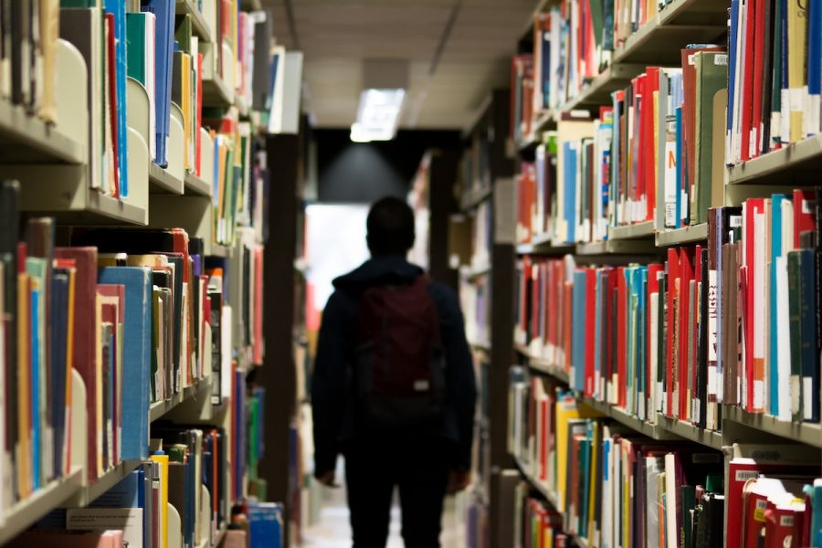 A student walks through a library.